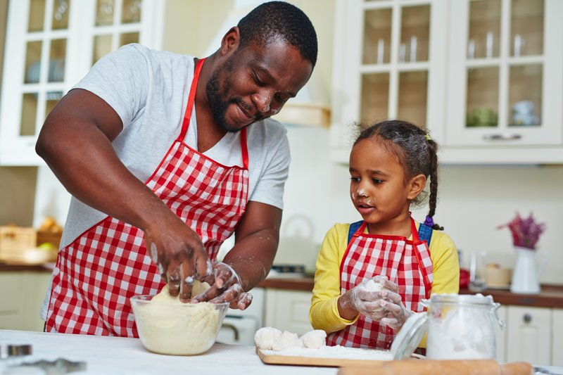 man and child cooking in a kitchen