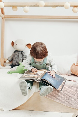 child reading wordless picture book while sitting on bed